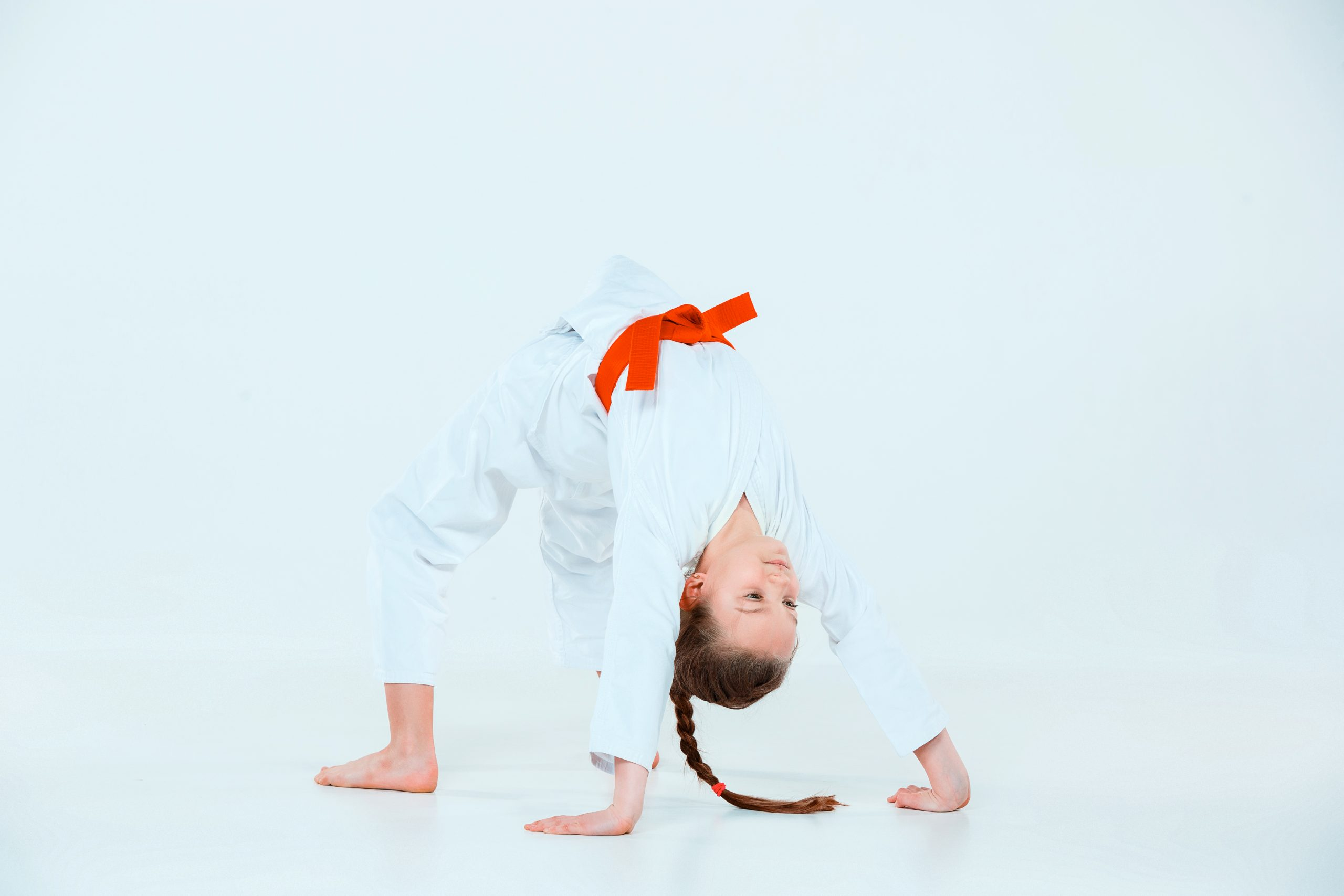 The teen girl posing at Aikido training in martial arts school. Healthy lifestyle and sports concept. Teenagers in white kimono on white background. stretch pose
